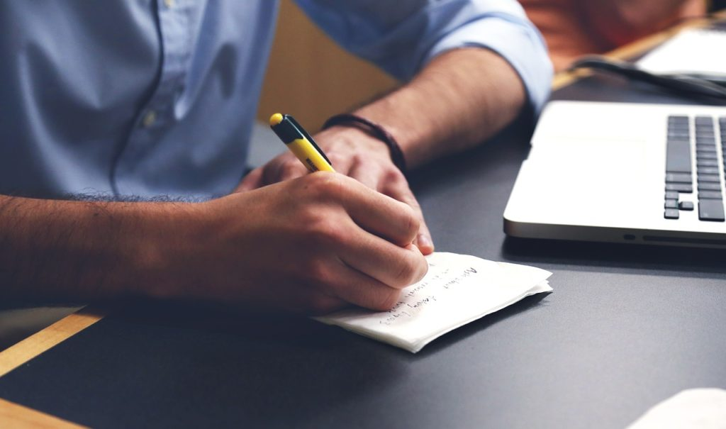 Hombre escribiendo un ensayo en una libreta