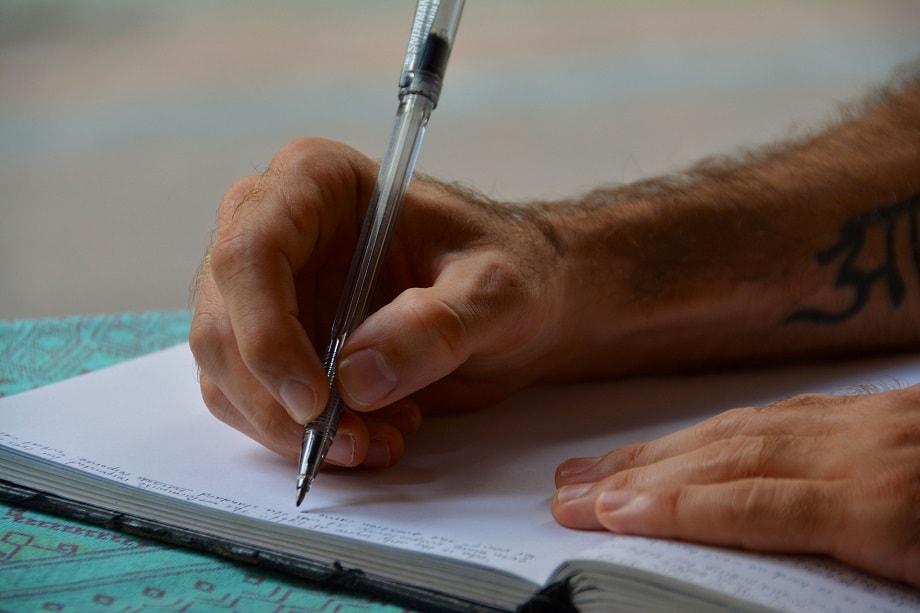 Hombre escribiendo para los concursos literarios de abril