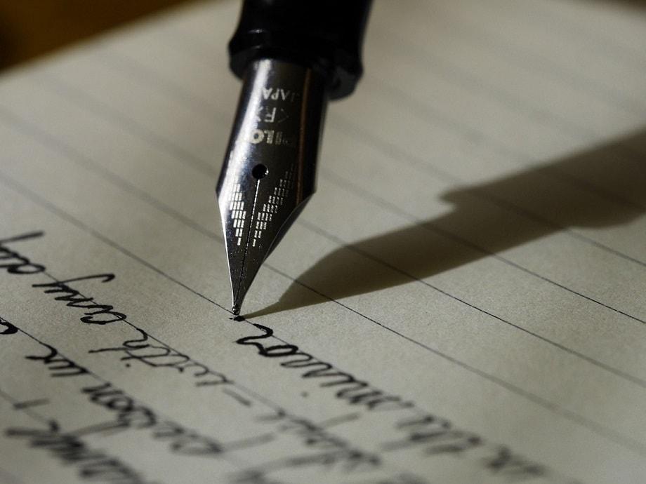 Pluma escribiendo sobre un cuaderno para los certámenes literarios de febrero