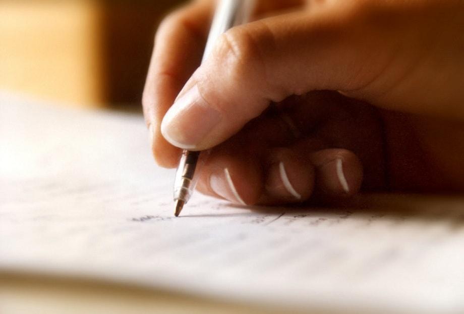 Chica escribiendo en una libreta para un certamen literario