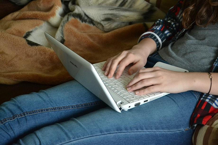 Autor novel o autora novel escribiendo en ordenador para uno de los concursos literarios de marzo