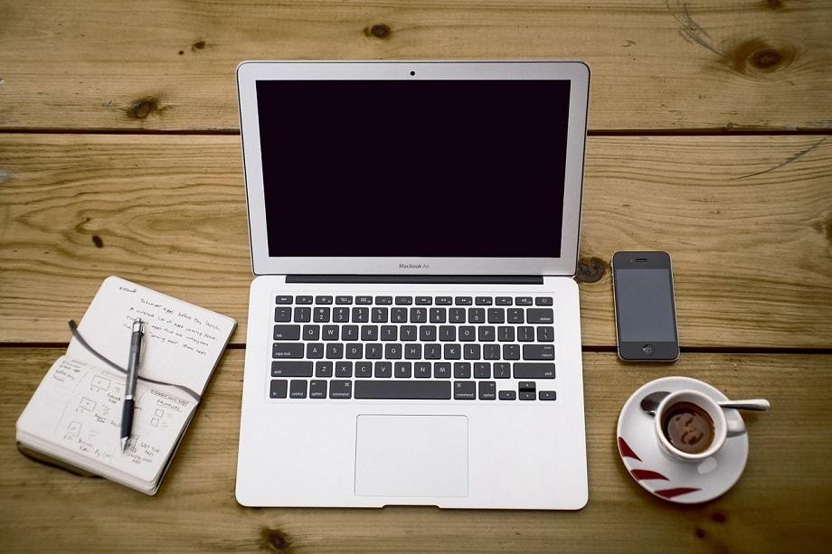 Portátil, libreta y bolígrafo para saber cómo empezar a escribir